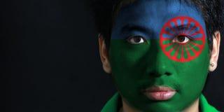 O retrato de um homem com a bandeira dos povos Romani pintou em sua cara no fundo preto imagem de stock