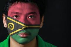 O retrato de um homem com a bandeira de Vanuatu pintou em sua cara no fundo preto fotos de stock royalty free