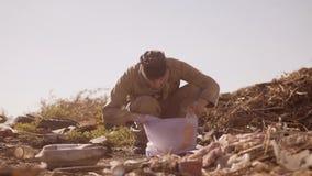 O retrato de um homem com fome desabrigado sujo em uma descarga bebe o suco faltante no pacote com passeio vai procurar video estoque