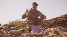 O retrato de um homem com fome desabrigado sujo em uma descarga bebe o suco faltante no pacote com passeio vai procurar filme