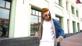 O retrato de um homem de cabelo vermelho novo na roupa à moda anda na cidade e decola seus óculos de sol vídeos de arquivo