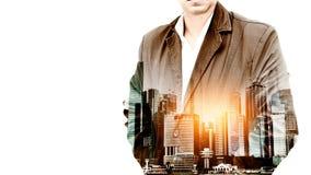 O retrato de um homem de negócios farpado seguro que está com suas mãos em uns bolsos overlay o fundo da paisagem da cidade Expos Fotografia de Stock