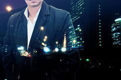 O retrato de um homem de negócios farpado seguro que está com suas mãos em uns bolsos overlay o fundo da paisagem da cidade da no foto de stock royalty free