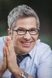 Retrato de um homem de negócios que sorri com suas mãos clasped imagens de stock royalty free