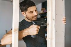 O retrato de um homem na roupa home com uma chave de fenda em sua mão fixa uma construção de madeira para uma janela em sua casa fotos de stock