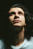 O retrato de um homem novo considerável com cabelo longo olha acima Foto de Stock