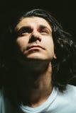O retrato de um homem novo considerável com cabelo longo olha acima Imagens de Stock