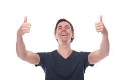 O retrato de um homem novo feliz com polegares levanta o gesto Fotografia de Stock