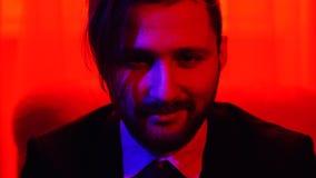 O retrato de um homem de sorriso farpado do negócio vestiu-se em um terno de negócio que senta-se na luz vermelha brilhante video estoque