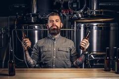 O retrato de um homem tattooed pensativo do moderno com barba à moda e o cabelo guardam duas garrafas com cerveja do ofício no in foto de stock