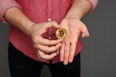 O retrato de um indivíduo novo em uma camisa vermelha e um bitcoin inventam no seu Imagens de Stock Royalty Free
