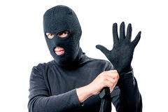 O retrato de um ladrão em uma máscara em sua cara endireita uma luva fotos de stock