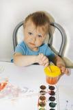 O retrato de um menino considerável está guardando uma escova de pintura Fotos de Stock