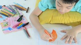 O retrato de um menino feliz asiático pequeno que tira um esboço, palavra é eu te amo filme