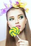 O retrato de um modelo com colorido compõe e doces no fundo branco Imagens de Stock