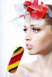 O retrato de um modelo com colorido compõe e doces no fundo branco Fotos de Stock