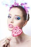 O retrato de um modelo com colorido compõe e doces no fundo branco Foto de Stock
