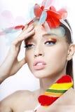 O retrato de um modelo com colorido compõe e doces no fundo branco Imagens de Stock Royalty Free