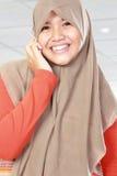 O retrato de um muçulmano asiático caçoa a fala no telefone celular fotografia de stock royalty free
