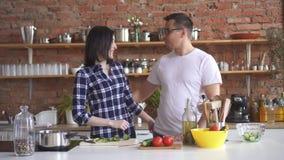 O retrato de um par novo na cozinha, menina corta vegetais e dá a um homem uma tentativa video estoque