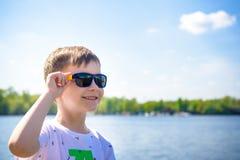 O retrato de um rapaz pequeno bonito com óculos de sol, sentando-se pelo rio - o lago e aprecia o dia bonito e ensolarado Fotografia de Stock