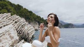 O retrato de um turista atrativo da mulher veste os óculos de sol que sentam-se em uma rocha, admirando a vista bonita por nature video estoque