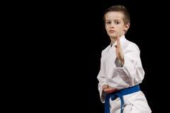 O retrato de uma criança do karaté no quimono pronto para lutar isolou-se no fundo preto fotografia de stock