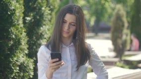 O retrato de uma jovem mulher em uma camisa branca usa um smartphone na tarde em uma rua na cidade filme
