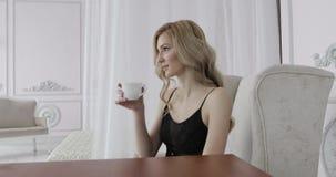 O retrato de uma jovem mulher em um roupa interior preto está bebendo o chá da manhã filme