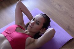 O retrato de uma jovem mulher executa um exercício nos músculos abdominais, levantando o torso acima Aptidão home fotografia de stock