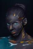 O retrato de uma jovem mulher que levantasse cobriu com a pintura preta Imagem de Stock Royalty Free