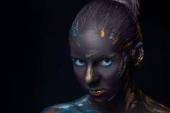 O retrato de uma jovem mulher que levantasse cobriu com a pintura preta Foto de Stock Royalty Free