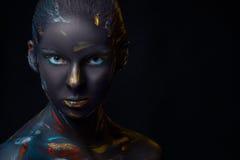 O retrato de uma jovem mulher que levantasse cobriu com a pintura preta Fotografia de Stock