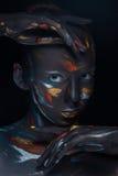 O retrato de uma jovem mulher que levantasse cobriu com a pintura preta Imagens de Stock Royalty Free