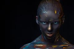 O retrato de uma jovem mulher que levantasse cobriu com a pintura preta Imagem de Stock