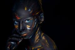 O retrato de uma jovem mulher que levantasse cobriu com a pintura preta Fotos de Stock Royalty Free