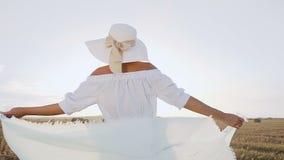 O retrato de uma menina atrativa em um vestido longo, óculos de sol, chapéu grande com um lenço gerencie ao redor ela mesma no ca filme