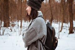 O retrato de uma menina bonita feliz com cabelo marrom na floresta do inverno vestiu-se em um estilo do moderno, estilo de vida Fotos de Stock Royalty Free