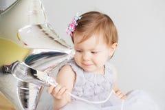 O retrato de uma menina bonita que guarda a prata estrela-deu forma à bola Fotografia de Stock Royalty Free