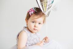 O retrato de uma menina bonita que guarda a prata estrela-deu forma à bola Imagens de Stock