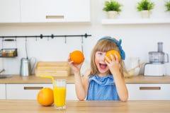 O retrato de uma menina em um vestido azul joga com laranjas em uma tabela fotos de stock royalty free