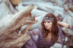 O retrato de uma menina em um vestido feericamente senta-se perto das árvores velhas Imagens de Stock