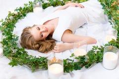 O retrato de uma menina de encontro, cabelo grosso que encontra-se messily, relance delicado dirigido de lado, as folhas verdes e fotografia de stock