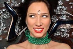 O retrato de uma menina moreno luxuoso encontra-se em um placer da joia dos diamantes, acessórios luxuosos fotografia de stock