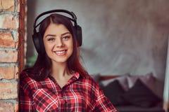O retrato de uma menina moreno de sorriso nos fones de ouvido vestiu-se em uma camisa e nas calças de brim de manta que inclinam- fotografia de stock royalty free