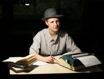 O retrato de uma menina que senta-se em uma tabela com uma máquina de escrever e os livros, pensa sobre a ideia na noite foto de stock royalty free