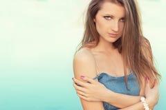 O retrato de uma menina 'sexy' bonita com as grandes ondas gordas dos bordos em um vestido da sarja de Nimes está nos bancos do r Fotos de Stock