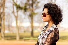O retrato de uma menina 'sexy' bonita com os bordos vermelhos morenos com ondas anda no parque Fotografia de Stock