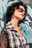 O retrato de uma menina 'sexy' bonita com os bordos vermelhos morenos com ondas anda no parque Foto de Stock Royalty Free
