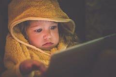 O retrato de uma menina vestiu-se no nightrobe que se senta no sofá e se guarda um tablet pc Imagens de Stock Royalty Free